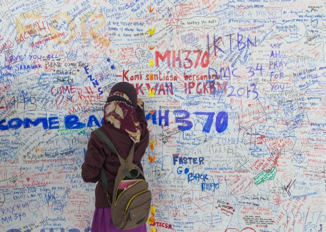 KUALA LUMPUR INTERNATIONAL AIRPORT - MARCH 17: Unidentified Muslim girl writes messages and prayers for Malaysia Airlines Boeing 777-200ER MH370 on March 17, 2014 in KLIA, Sepang, Malaysia.